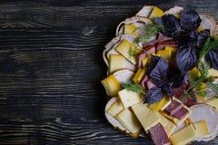 Salami, jam?n y ensalada cortada y verduras del queso Exprimir la salchicha y la carne curada en una tabla festiva imagenes de archivo