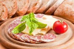 Salami, Käse, Brot ciabatta, Basilikum und Tomate Lizenzfreie Stockfotografie