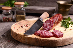 Salami and knife. On a cutting board Stock Photos