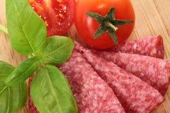 Salami med tomaten och basilika 免版税图库摄影