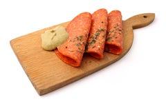 Salami met mosterd op een scherpe raad Stock Foto's