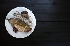 Salami met vorm op witte plaat op donkere houten achtergrond, bovenkant v Royalty-vrije Stock Foto's