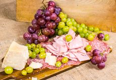 Salami, mortadella, cheese, yellow and red muscat grape on a wooden board and canvas Stock Photos