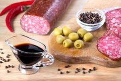 Salami, olive, épice sur la planche à découper sur la table en bois Images stock