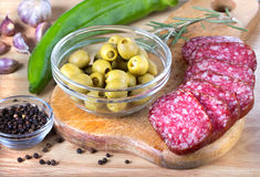Salami, olive sur la planche à découper sur la table en bois Photo libre de droits