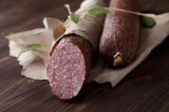 Salami on wooden and paper. Salami on paper on dark wooden table stock images