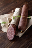 Salami on wooden and paper Royalty Free Stock Images