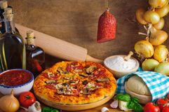 Salami pizza. Traditional homemade salami pizza with ingredients stock photo