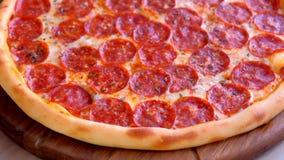 Salami pizza na drewnianej desce na stole blisko lily farbuje mi?kki na widok wody zbiory wideo