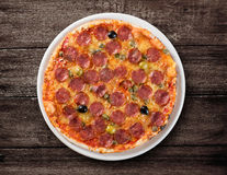 Salami pizza top view on wooden table Royalty Free Stock Photography