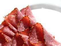 Salami on plate. Cut salami on white plate royalty free stock photo