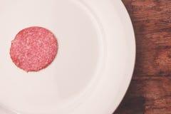 Salami on plate Stock Photos