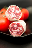 Salami on plate with tomatoes close up Stock Photography
