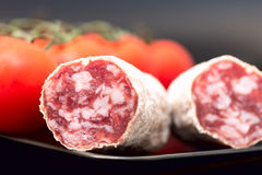 Salami on plate with tomatoes Royalty Free Stock Images