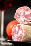 Salami on plate with tomatoes and red wine shallow DOF Royalty Free Stock Photos