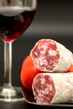 Salami on plate with tomatoes and red wine vertical Stock Image