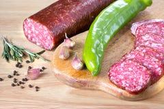 Salami, poivron vert, ail sur la table de cuisine en bois Photos libres de droits