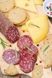 Salami, queso y galletas italianos en una tabla de cortar imágenes de archivo libres de regalías