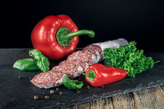 Salami with red paprika and pepper. On the slate board Royalty Free Stock Images