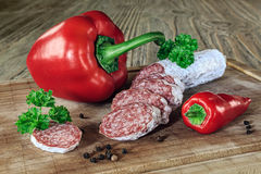 Salami with red paprika and pepper. On the wooden table Royalty Free Stock Images