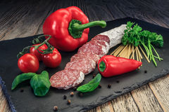 Salami with red paprika, tomatoes and pepper. Salami with red paprika, tomatoes  and pepper on the slate board Royalty Free Stock Photo