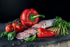 Salami with red paprika, tomatos  and pepper on the slate board Stock Image