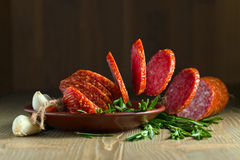 Salami with rosemary. On a old wooden table Royalty Free Stock Photo