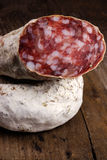 Salami on rustic wooden board stock images