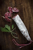 Salami and Sage. Spanish Fuet Salami and Fresh Sage on Rustic Wooden Cutting Board Royalty Free Stock Photography
