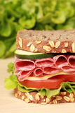 Salami Sandwich. Close-up of a fresh sandwich with salami, cheese and lettuce on a wooden table stock image