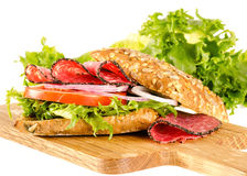 Salami sandwich with full-corn bread on cutting board on white Stock Image