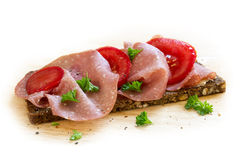 Salami sausage and sliced tomato on a dark whole grain bread wit Stock Image