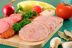 Salami and sausage slices and vegetables Royalty Free Stock Photography
