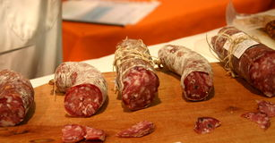 Salami sausages. Five italian salami sausages with a thin slice of each in front of them Stock Photo