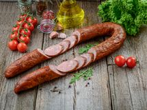 Salami sausages sliced with pepper, garlic and rosemary on cutting board royalty free stock photo