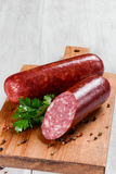 Salami sausages sliced with pepper, garlic and rosemary on cutting board on wooden table. Stock Images