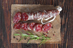 Salami sausages sliced. With pepper and rosemary on old wooden table, top view stock photography