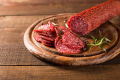 Salami sausages on a wooden table Royalty Free Stock Images