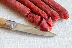 Salami with a sharp knife Stock Images