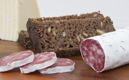 Salami, sheese, bread. On wooden background Royalty Free Stock Photos