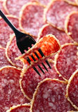 Salami slice on a fork Royalty Free Stock Images