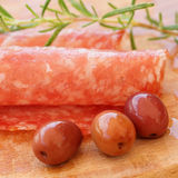Salami slice, rosemary herb, olives Royalty Free Stock Image