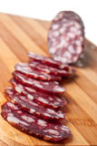 Salami sliced on chopping board Stock Photos