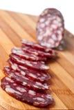 Salami sliced on chopping board Stock Photos