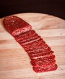Salami sliced on chopping board stock image
