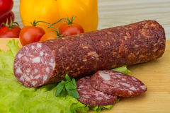 Salami. Sliced Salami with salad leaves on the wood background stock images