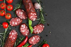Salami sliced with tomatoes, rosemary and peppercorns on black slate background. Salami sausage. top view