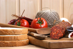 Salami and  slices bread on a timber board Royalty Free Stock Images
