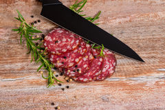 Salami slices with pepper and rosemary Royalty Free Stock Photo