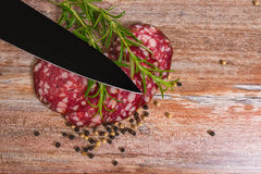 Salami slices with pepper and rosemary Stock Photography